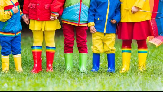 Kinder in Gummistiefeln mit Logo